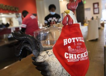 """A bib wraps a chicken sculpture as employees pack up takeout orders at the Hotville Chicken restaurant at Baldwin Hills Crenshaw in Los Angeles, California, November 24, 2020. – It's been a rough year for Black-owned small businesses, and the latest surge in coronavirus cases suggests a festive season without much celebration.""""Black Friday"""" normally kicks off the holiday shopping season the morning after Thanksgiving. But rising coronavirus cases have prompted fresh restrictions in Los Angeles and elsewhere.The new rules mean Hotville Chicken, a south Los Angeles restaurant specialzing in """"Nashville-style"""" spicy dishes, will have to shut its outdoor eating space after already closing the dining room. (Photo by Patrick T. Fallon / AFP)"""