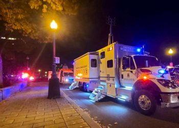 """A Police truck is parked near the National Assembly of Quebec, in Quebec City, early on November 1, 2020, after two people were killed and five wounded by a sword-wielding suspect dressed in medieval clothing. The suspect, """"a man in his mid-20s,"""" was armed with a sword and dressed in """"medieval clothing,"""" Quebec City police spokesman Etienne Doyon said during a press briefing. The man, who was not identified, was arrested shortly before 1:00 am and had been """"transported to hospital for evaluation,"""" he said.Jordan PROUST / AFP"""