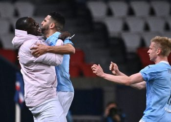 Manchester City's Algerian midfielder Riyad Mahrez (C) celebrates after scoring a goal with Manchester City's French defender Benjamin Mendy (L) and Manchester City's Ukrainian midfielder Oleksandr Zinchenko during the UEFA Champions League first leg semi-final football match between Paris Saint-Germain (PSG) and Manchester City at the Parc des Princes stadium in Paris on April 28, 2021. Anne-Christine POUJOULAT / AFP