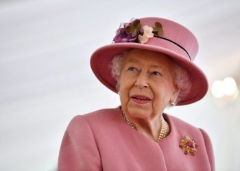 """(FILES) In this file photo taken on October 15, 2020 Britain's Queen Elizabeth II speaks with staff during a visit to the Defence Science and Technology Laboratory (Dstl) at Porton Down science park near Salisbury, southern England. – Queen Elizabeth II is saddened by the challenges faced by her grandson Prince Harry and his wife Meghan, and takes their allegations of racism in the royal family seriously, Buckingham Palace said on March 9, 2021. """"The whole family is saddened to learn the full extent of how challenging the last few years have been for Harry and Meghan. The issues raised, particularly that of race, are concerning,"""" the palace said in a statement released on the queen's behalf. (Photo by Ben STANSALL / POOL / AFP)"""