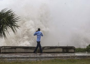 A man records a video of the strong waves during the passage of storm Elsa at the MalecÛn in Santo Domingo, on July 3, 2021. (Photo by Erika SANTELICES / AFP)