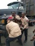 PHOTOS: Angry mob pounce on FRSC official in Delta for allegedly pushing driver off his
