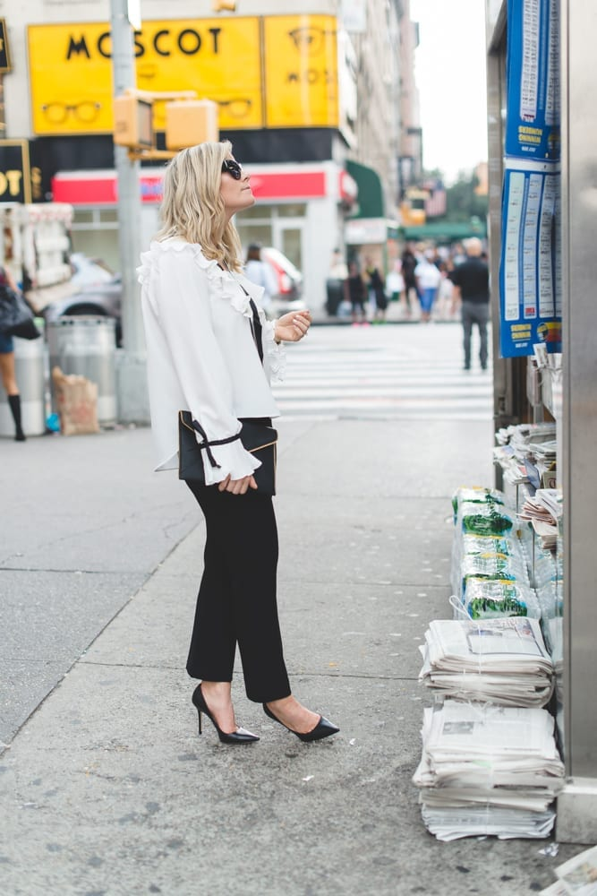 Blogger, Ashley Pletcher browses a newsstand for the latest celebrity gossip wearing an Asos ruffle top with Express pants and Jimmy Choo Pumps and Rebecca Minkoff envelope clutch.