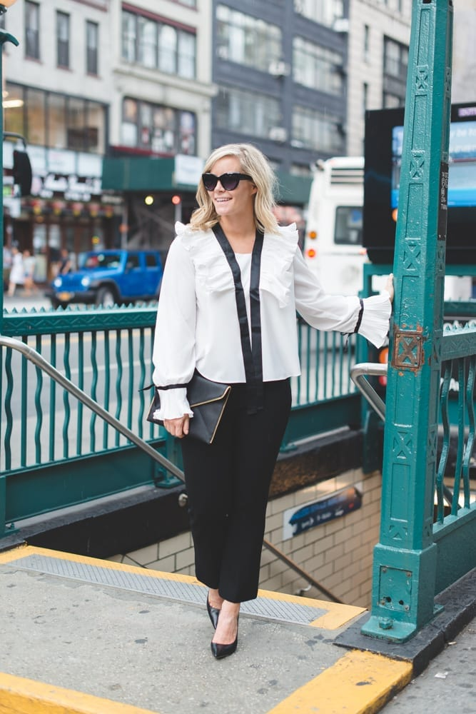 In between NYFW shows, blogger, Ashley Pletcher, hops off the NYC subway wearing an Asos ruffle top with Express pants and Jimmy Choo Pumps!