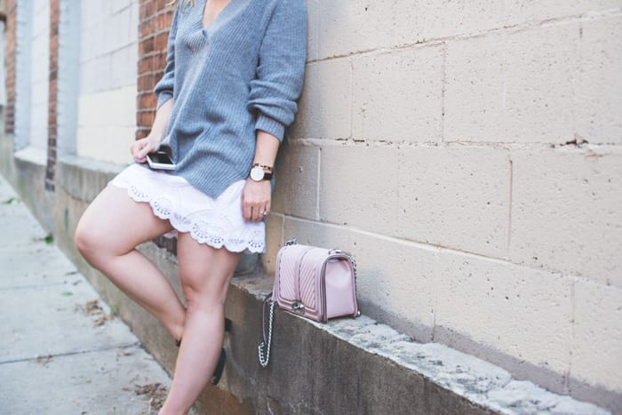 Fashion Blogger, Ashley Pletcher starts transitioning clothing into a Fall wardrobe with blush and grey by pairing an Abercrombie & Fitch summer skirt with some black booties and a Nordstrom deep v-neck sweater, and a classic Daniel Wellington watch.