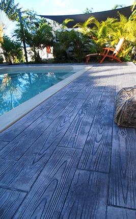 Terrasse en béton imprimé à côté d'une piscine