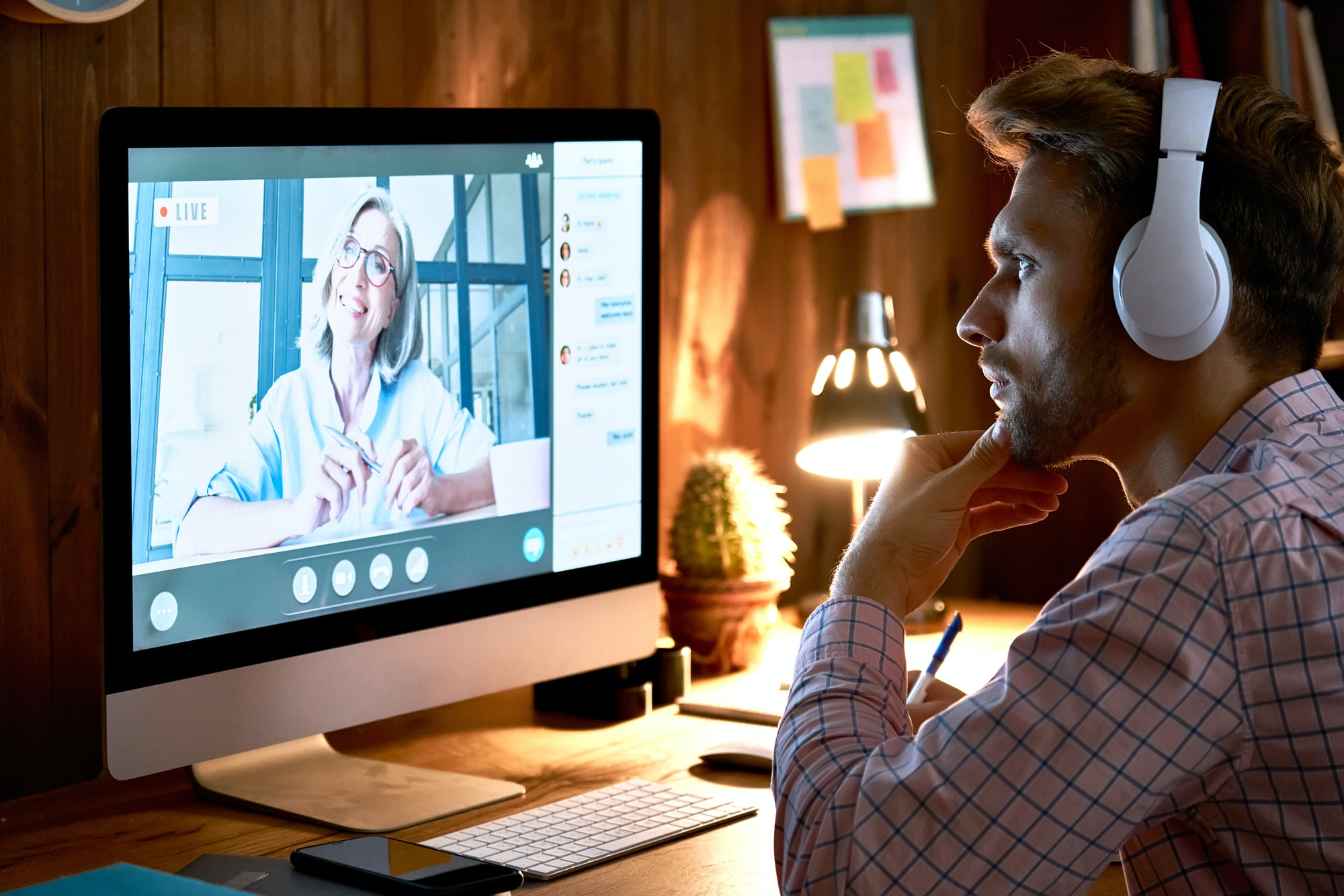 Serious male student wearing headphones taking online course, watching webinar.