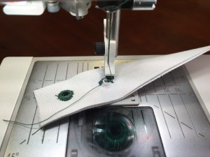 Rotate the fabric around the eyelet plate while sewing with a zig zag stitch.
