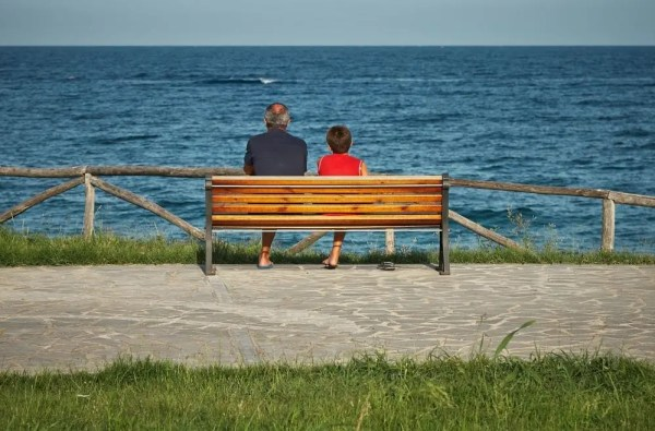 grandfather and grandson on a bench looking at the sea