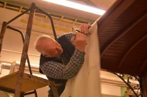 Lasse arbetar med att fästa takväven. Foto: Yngve CG
