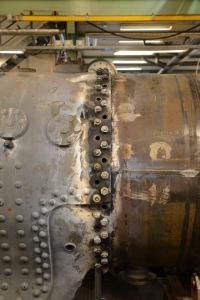 """Nitning av ångpannan närmar sig. M22-bultarna skall nu ersättas av nitar i 7/8""""-dimension. För att förbandet ska hålla ihop under tiden tas till att börja med var tredje bult ur. Sedan nitas ett varv, och processen upprepas två gånger till. Sedan skall plåtskarvarna diktas innan det är klart. Foto: Marcus Jacobson"""