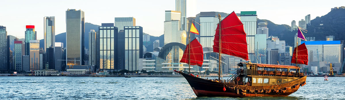 Junk boat in Victoria Harbour with Hong Kong skyline in background