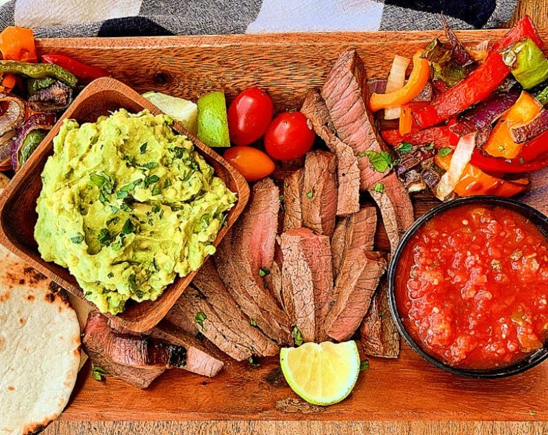 wood board with medium rare sliced steak, caramelized onions and bell peppers and bowls of salsa and guacamole