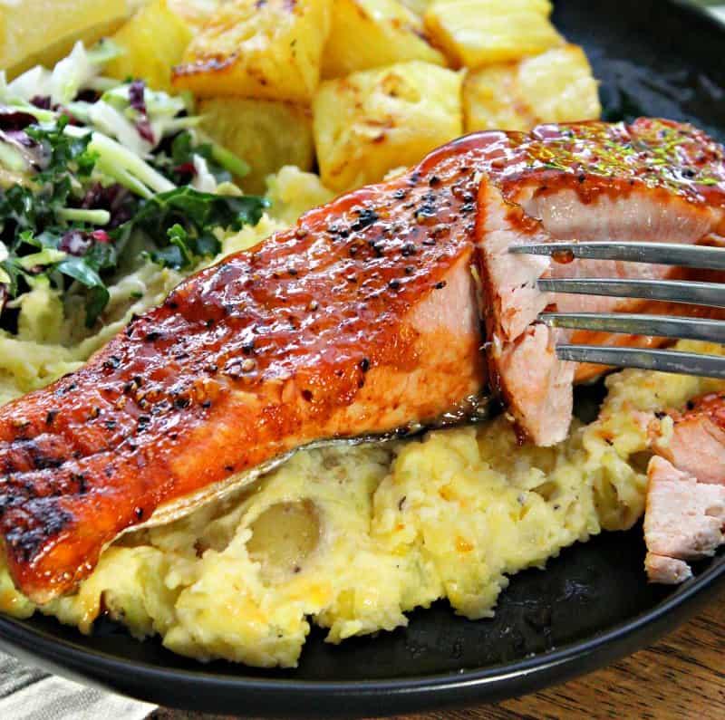 black plate with teriyaki salmon filet, mashed potatoes, slaw and pineapple chunks