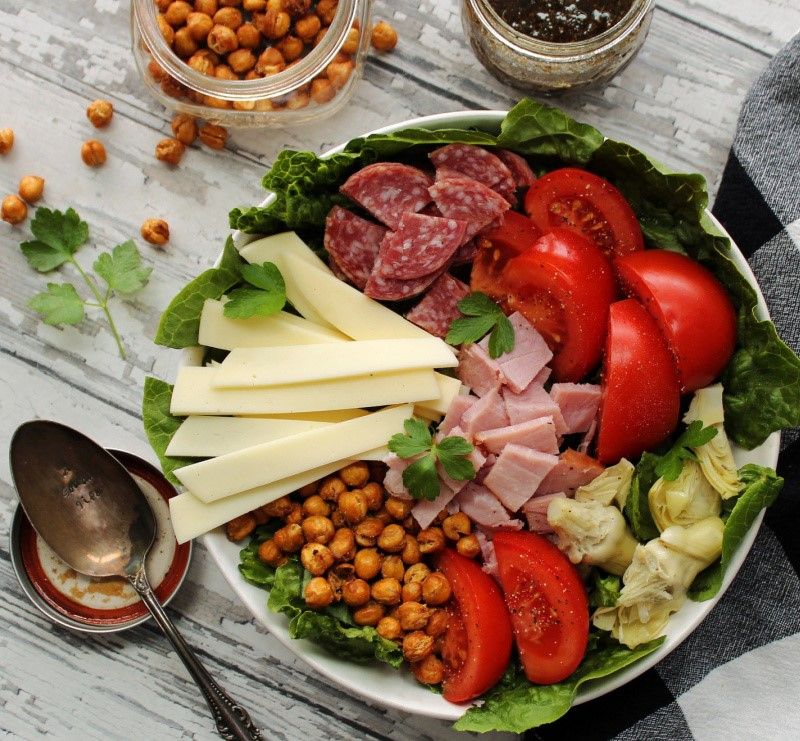 overhead view antipasto salad in bowl with jar of dressing