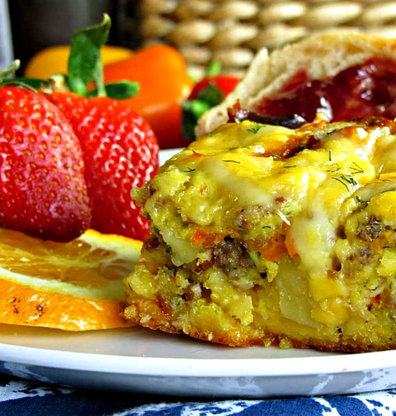 square of egg sausage casserole on white plate with fresh berries on side