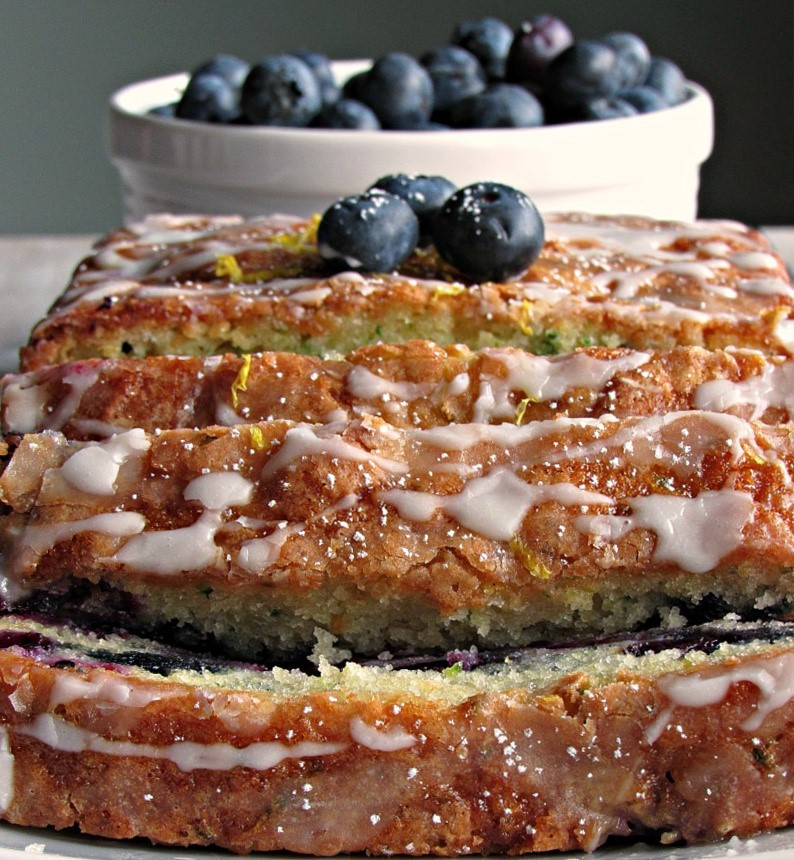 loaf of blueberry zucchini bread sliced on white plate