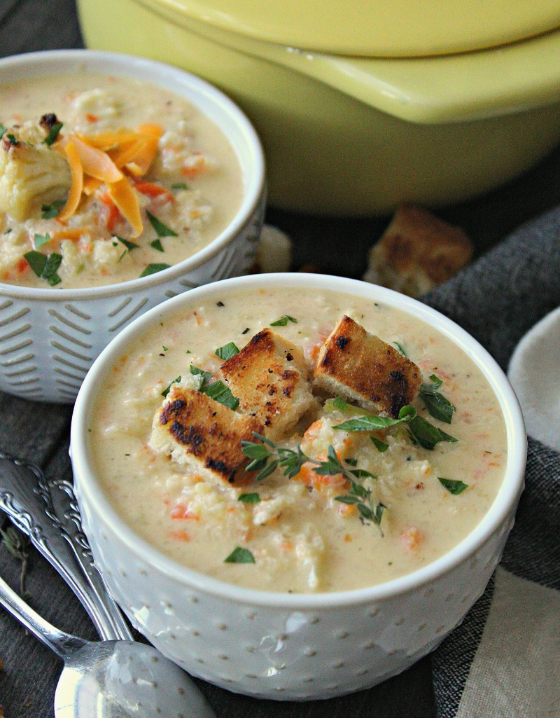 bowl of roasted cauliflower soup topped with croutons and cheddar cheese
