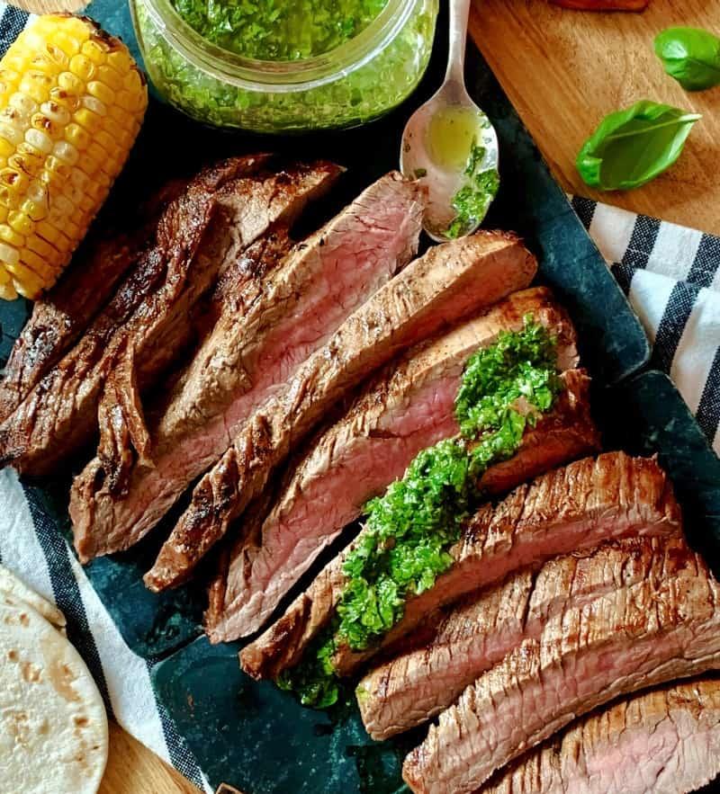 overhead sliced steak drizzled with basil chimichurri