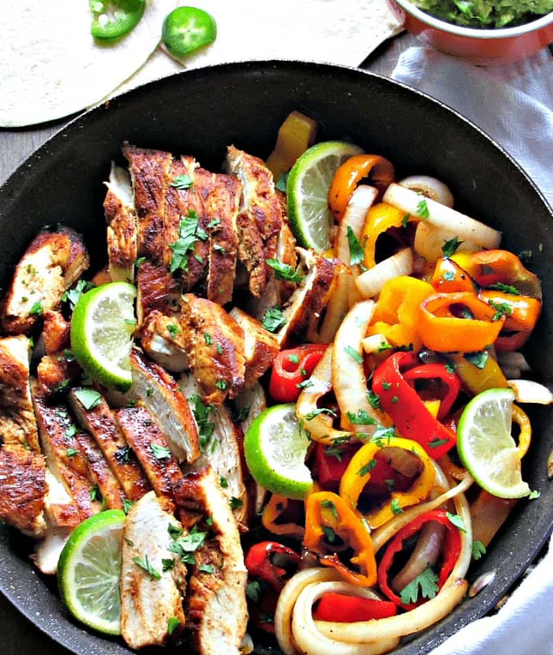 sliced chicken, peppers and onions in skillet