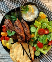 black plate with 3 kofta kabobs, side salad, naan bread and a small bowl of garlic sauce