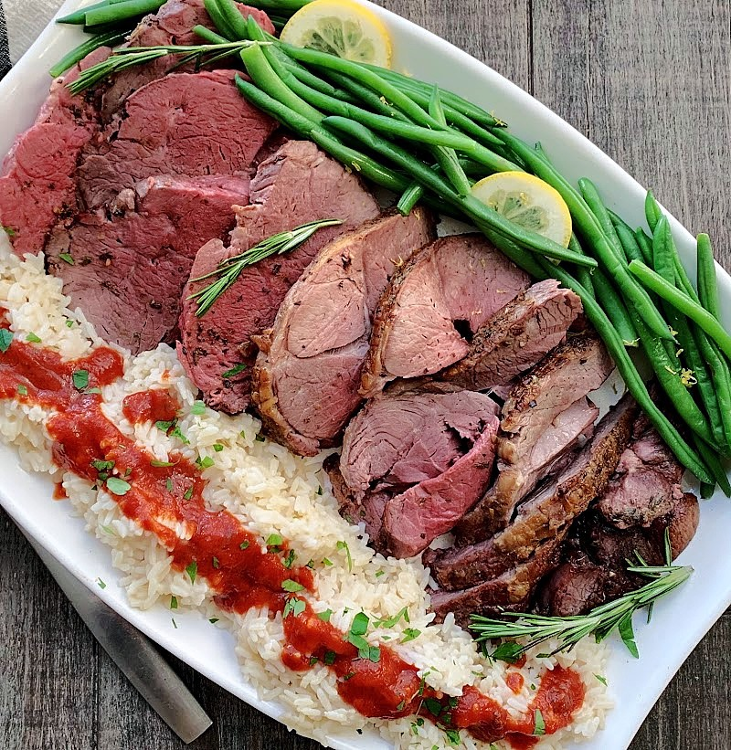 sliced lamb on white platter with rice and green beans
