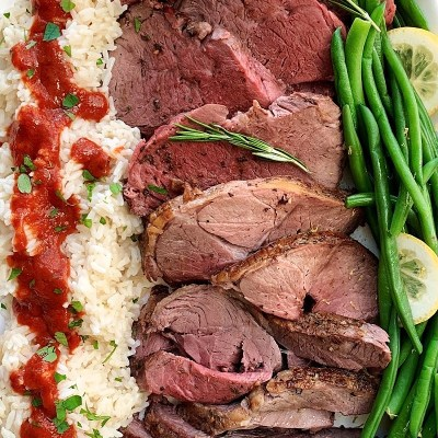 sliced roast of lamb with rice and green beans on white platter