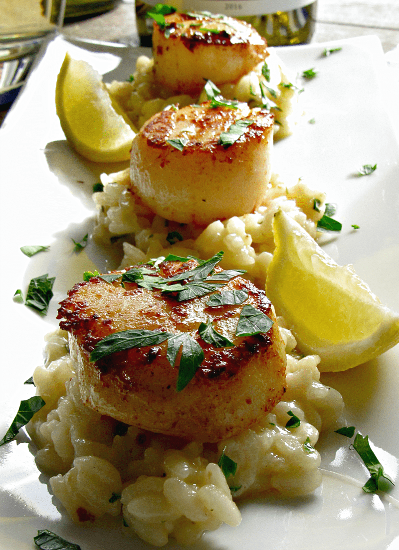 seared scallops on a bed of risotto garnished with parsley and lemon wedges