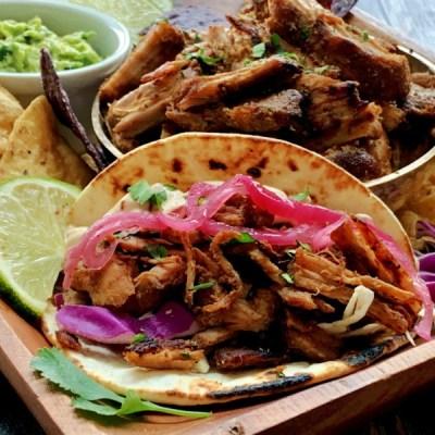 carnitas taco in flour tortilla with bowl of carnitas also shown