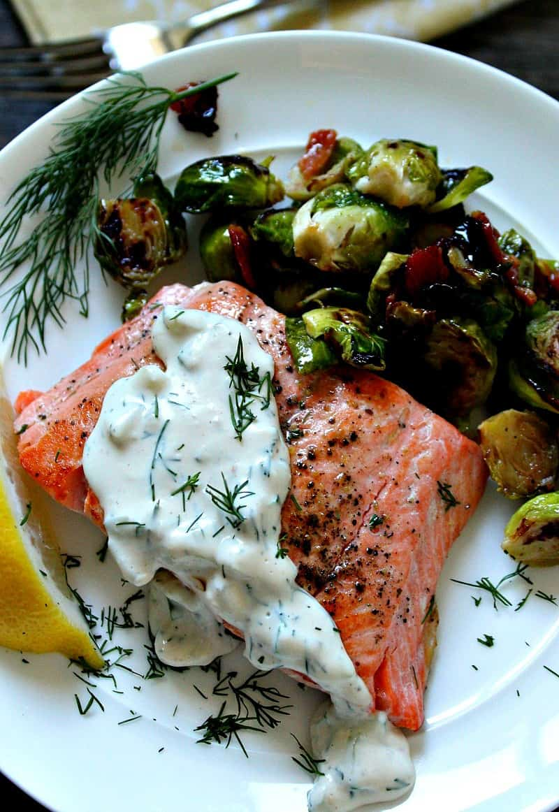 salmon filet topped with creamy sauce served with brussels sprouts