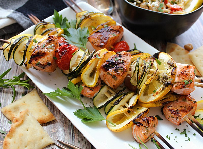 white plate with 3 salmon and vegetable kabobs