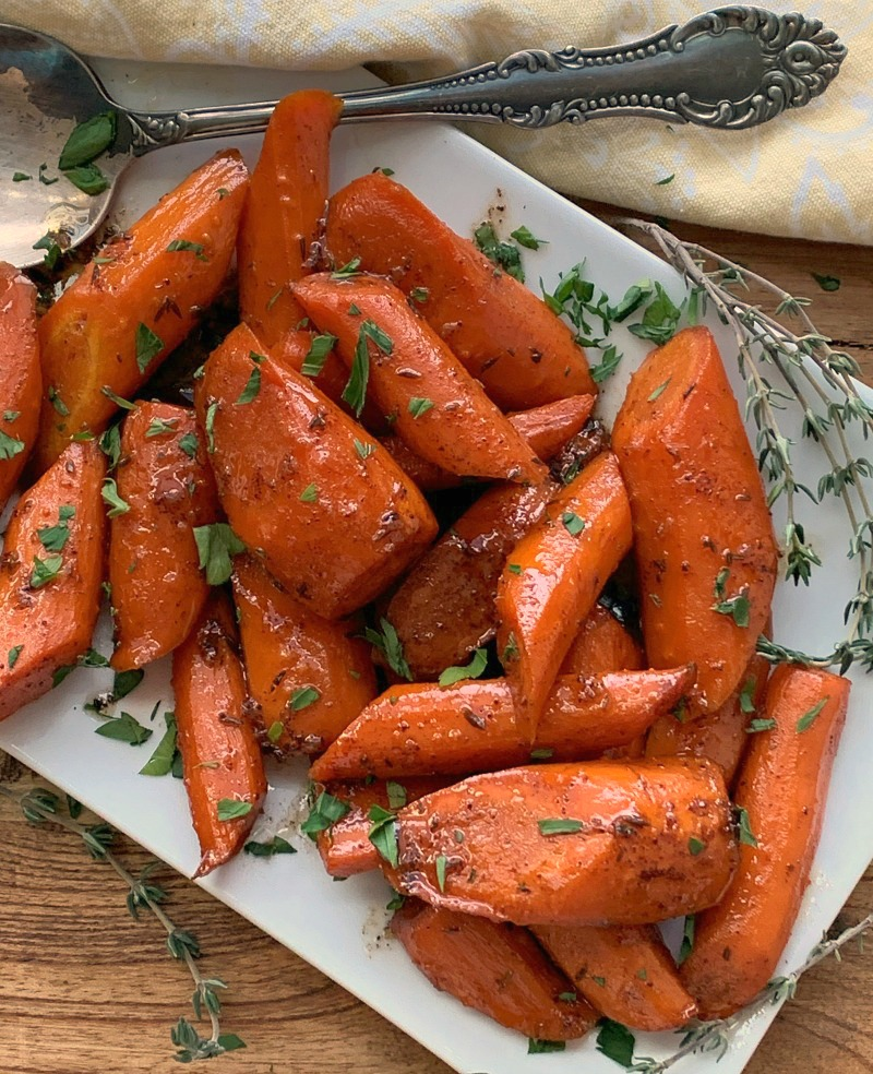 white plate with slow cooker glazed carrots garnished with parsley