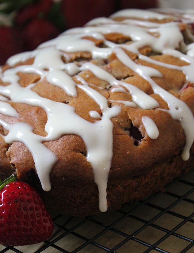 glazed strawberry bread before slicing garnished with fresh berries