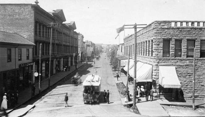 View of West Cordova from Carrall Street, showing brick buildings on either side of street with tramcar on road.