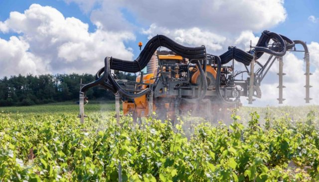 Una macchina agricola sparge pesticidi
