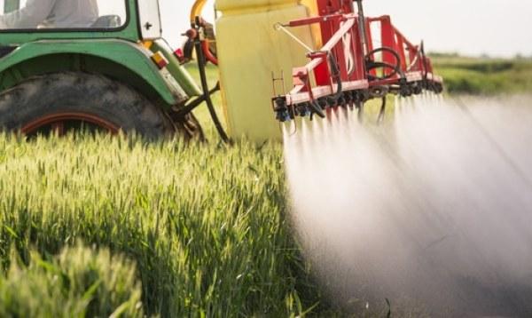 Un mezzo agricolo sparge pesticidi su un campo