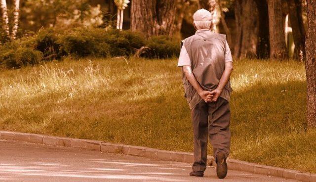 Uomo anziano cammina su strada deserta