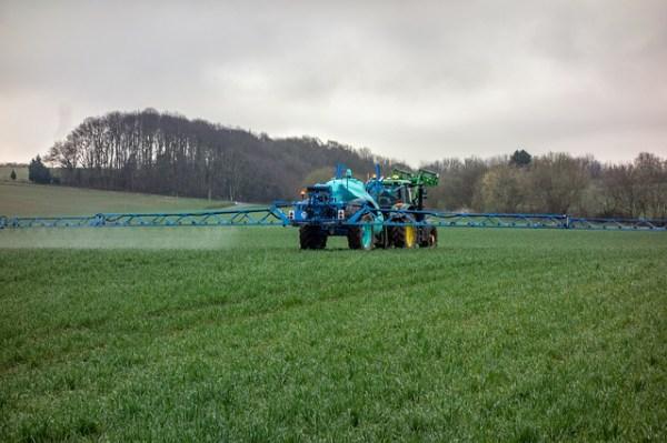 Un mezzo agricolo sui campi sparte pesticidi