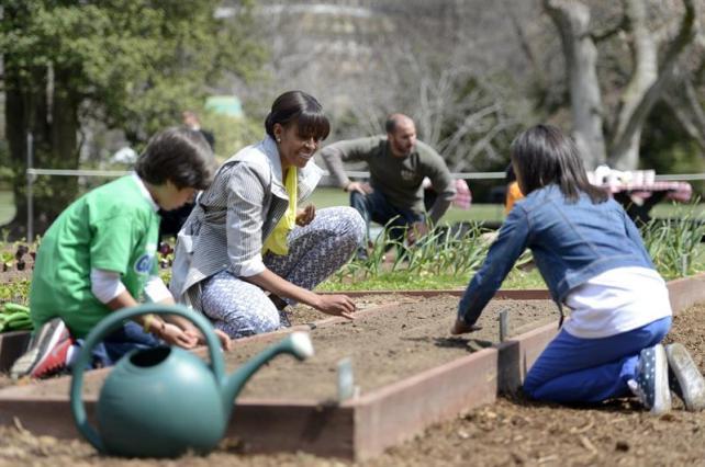 Michelle Obama en el huerto de la Casa Blanca plantando junto con algunos de los escolares estadounidenses invitados