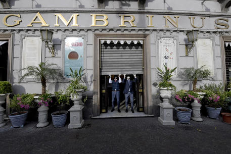 The reopening of the historic Gambrinus bar, in Naples, southern Italy, after the lockdown due to the Coronavirus emergency, 21 May 2020. Before raising the gate, managers and bartenders, espresso cups in hand, made a happy toast. Italy is gradually easing lockdown measures implemented to stem the spread of the SARS-CoV-2 coronavirus that causes the COVID-19 disease. ANSA / CIRO FUSCO