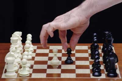 Person playing chess to learn the strategy of success