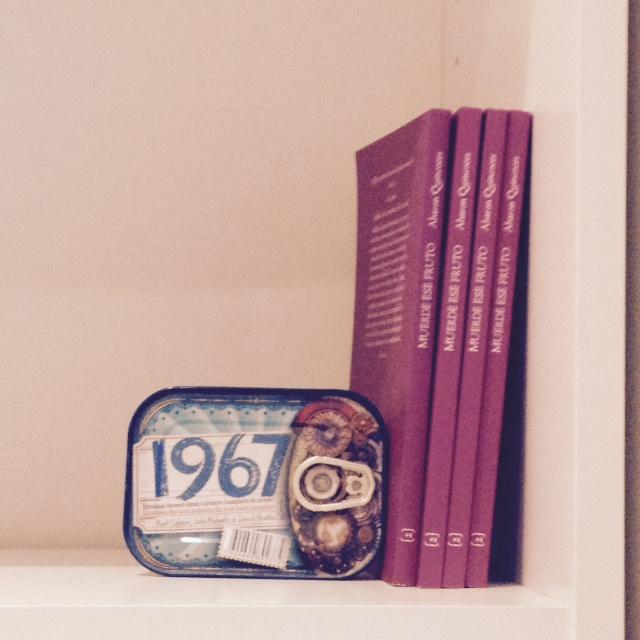 Varias copias de Muerde ese fruto en estantería, junto a una larte de sardinas con la fecha 1967.  #Libros