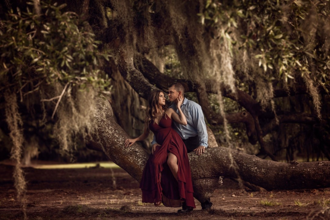 sexy engagement photo on tree with spanish moss