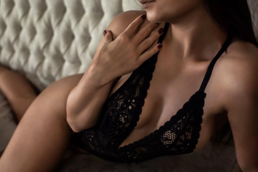 sexy closeup body shot of brunette in low cut black lace lingerie