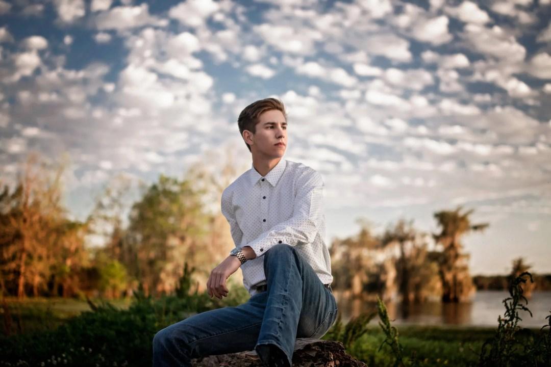 high school senior male lake photo shoot white button up shirt blue jeans