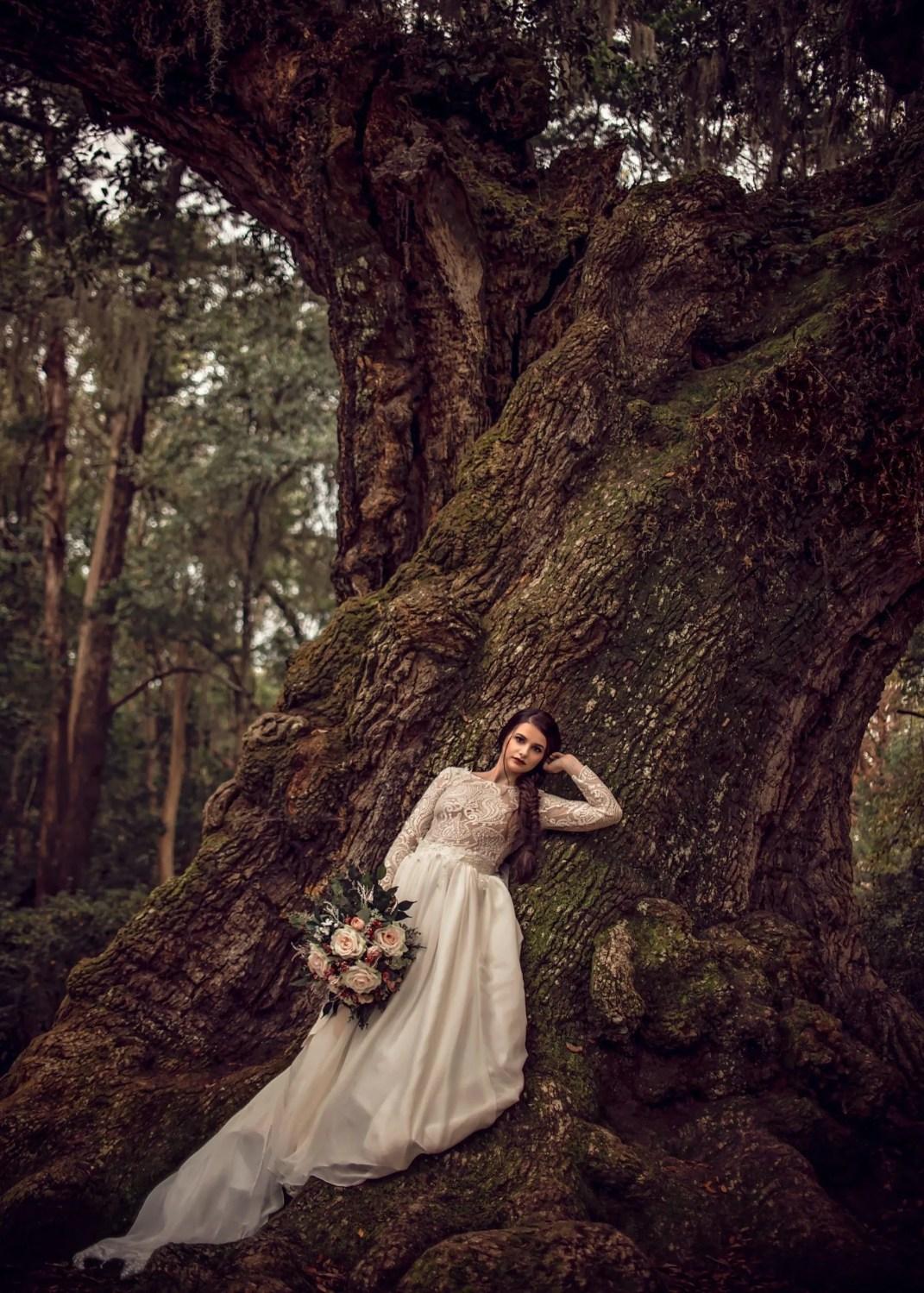 award winning bridal portrait of beautiful bride leaning on tree