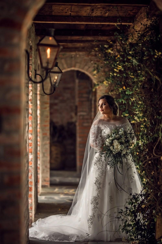 beautiful bride holding bouquet in walkway