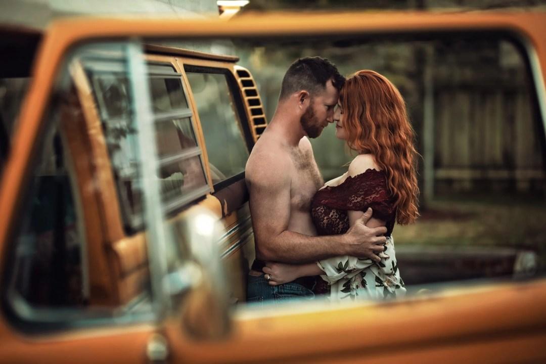 sexy couple engagement shoot beautiful redhead shirtless man holding close near vintage van