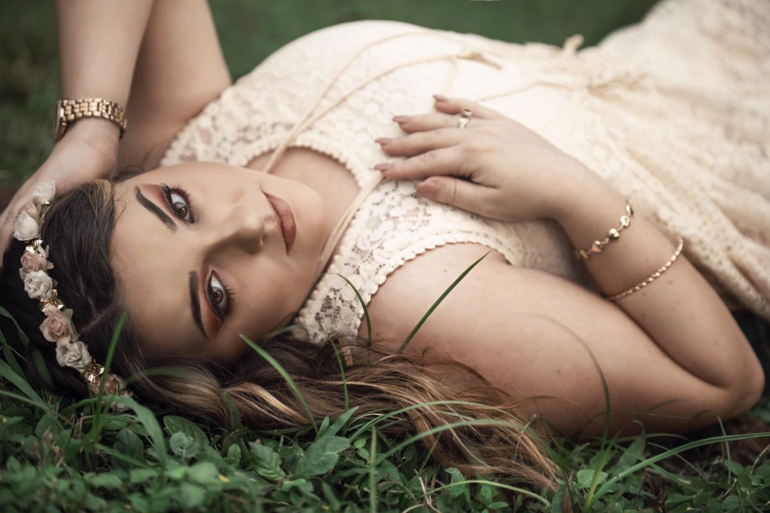 outdoor senior photography laying in grass with flower wreath