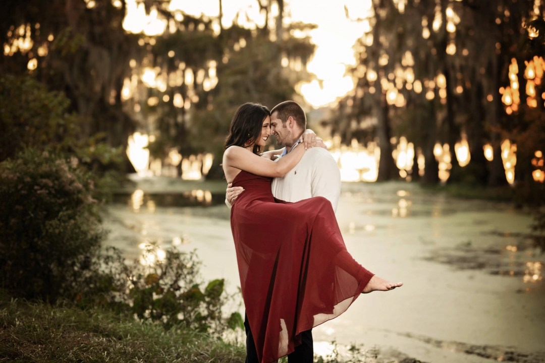 engagement picture in nature man holding woman in burgundy dress
